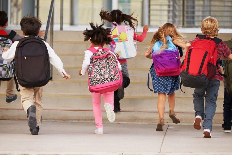 Deti bežiace do školy so školskými taškami na chrbtoch