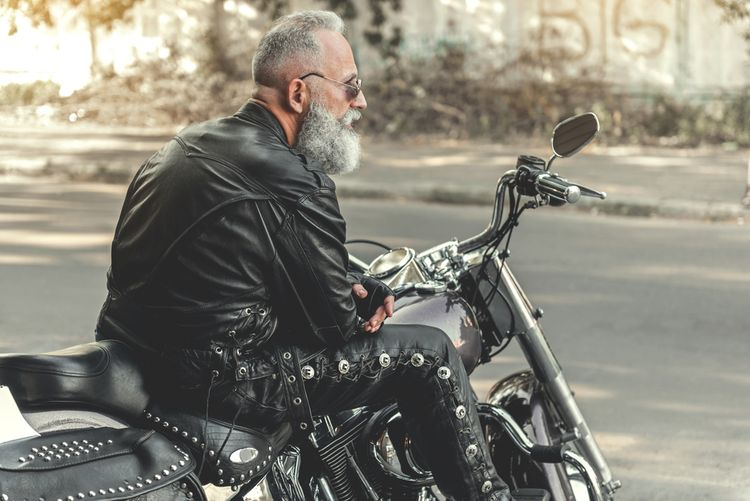 Motorkár v kožených nohaviciach a bunde sediaci na motorke