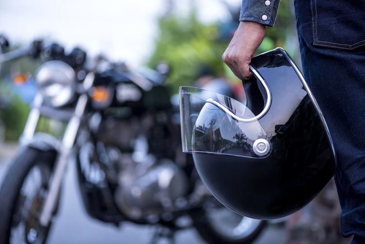 Mladý motorkár s prilbou na motorku v ruke