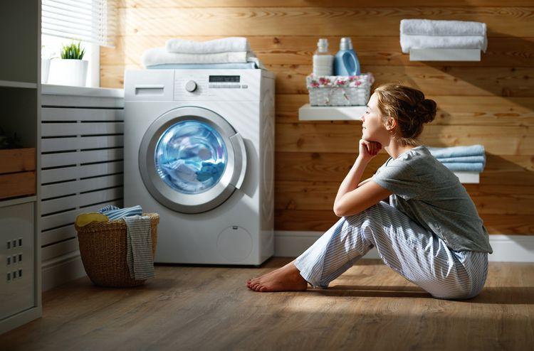Žena pozorujúca prací cyklus v spredu plnenej práčke