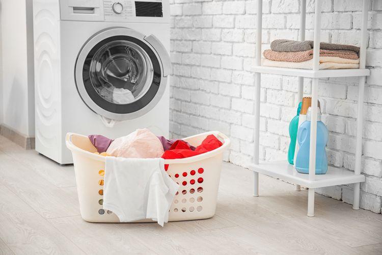 Spredu plnená práčka a bielizeň pripravená na pranie