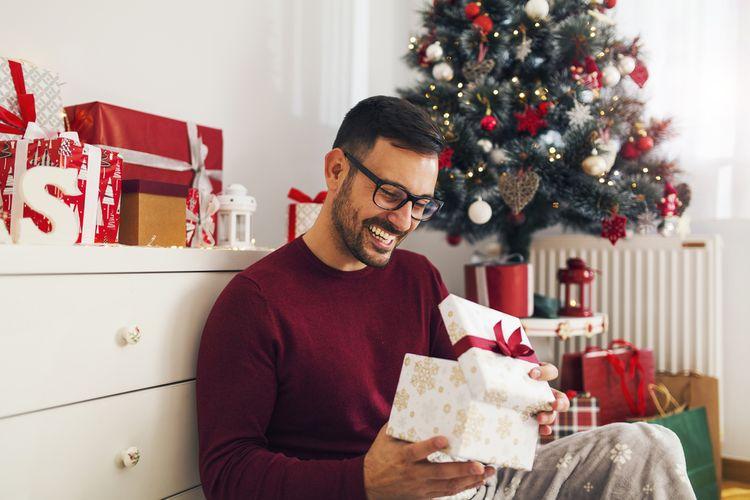 Muž otvárajúci darček na Vianoce