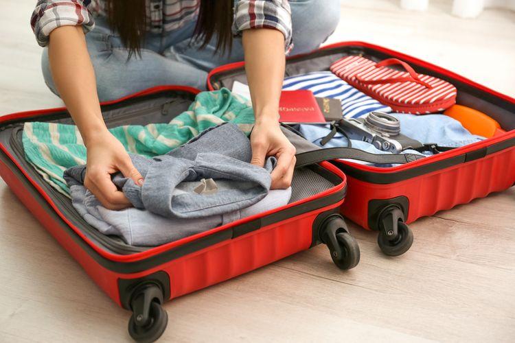Červený cestovný kufor - balenie sa na dovolenku