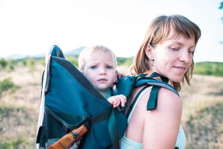 Dieťa sediace v turistickom nosiči