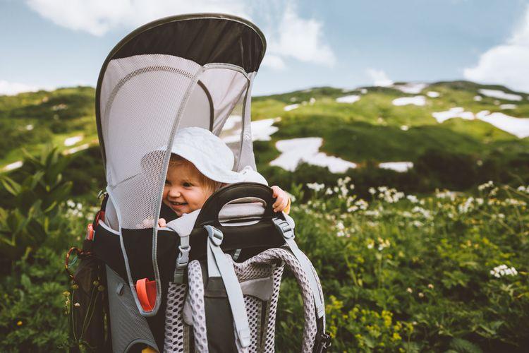 Dieťa v turistickom nosiči so strieškou