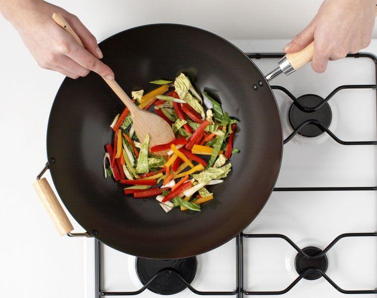 Príprava zeleniny v železnej wok panvici