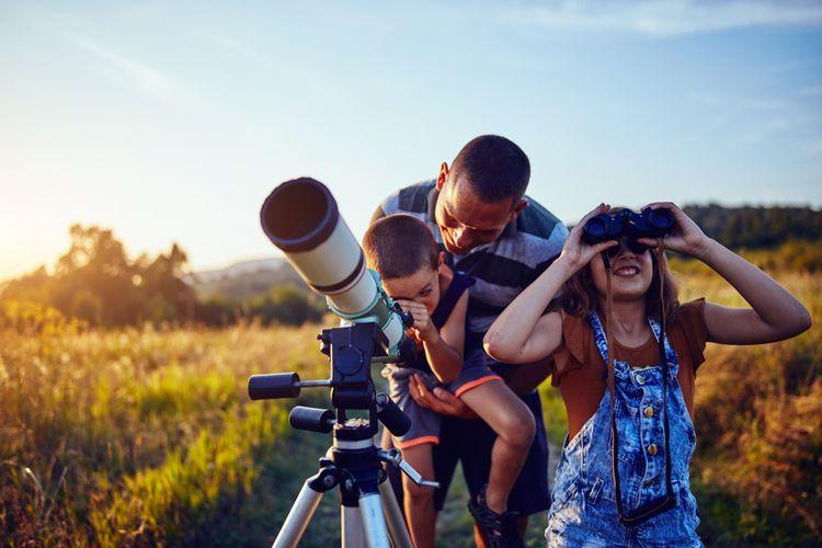 Rodina pozorujúca oblohu v prírode pomocou teleskopu