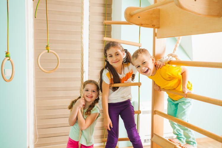 Deti cvičiace na drevených rebrinách s príslušenstvom