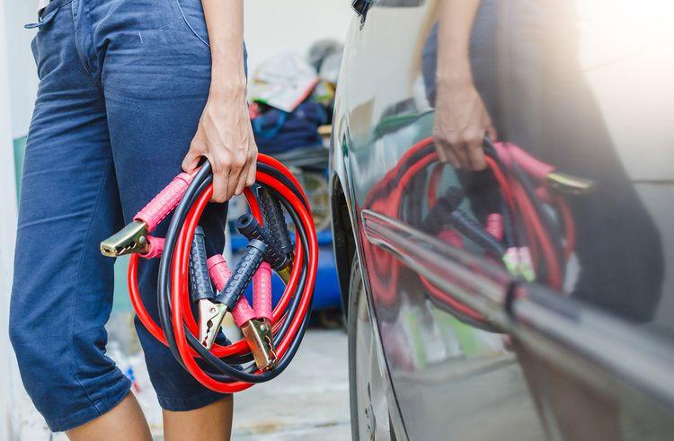 Žena so štartovacími káblami pri aute